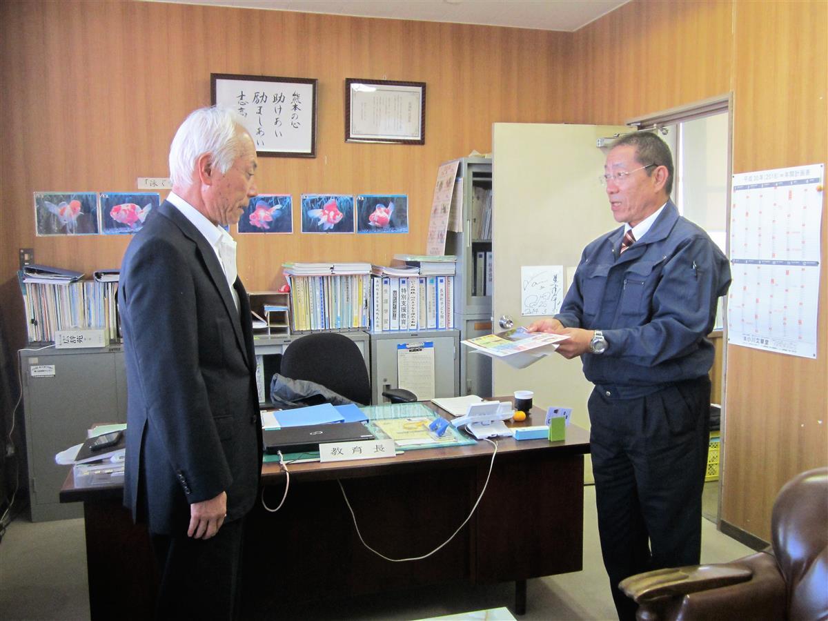下敷きを贈呈する市原地区長(右)